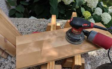 A wooden panel on a pair of low sawhorses with an orbital sander resting on top