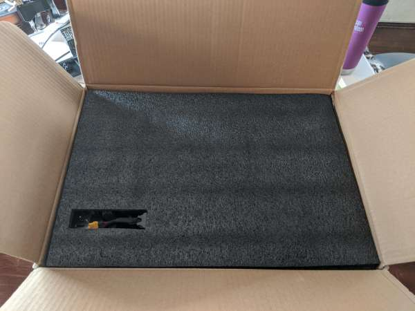 An open box with black foam. A small cutout on the lower left shows some cabling