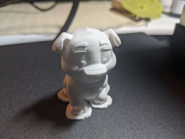 The completed dog print in white plastic, still sitting on the print bed.